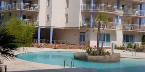 The bright, modern Port Canigo apartment features a private, furnished balcony overlooking the shared outdoor pool. It is located beside Aiguamolls Nature Reserve, 10 minutes' drive from central Roses.